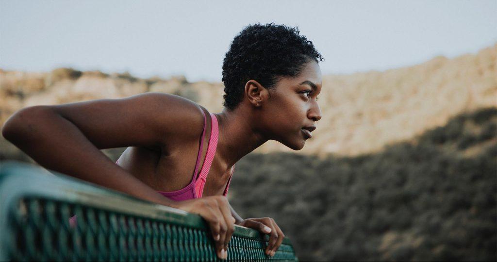 Mulher negra com roupa de ginástica tomando fôlego ao ar livre