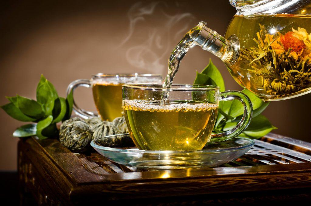 Bule despejando chá verde na xícara
