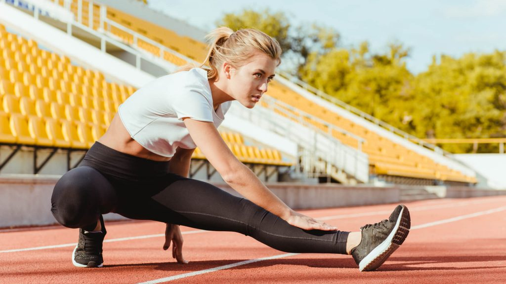 Mulher loira alongando a perna em pista de atletismo