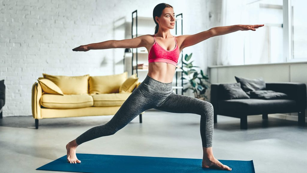 Mulher jovem morena fazendo uma postura de ioga na sala de casa
