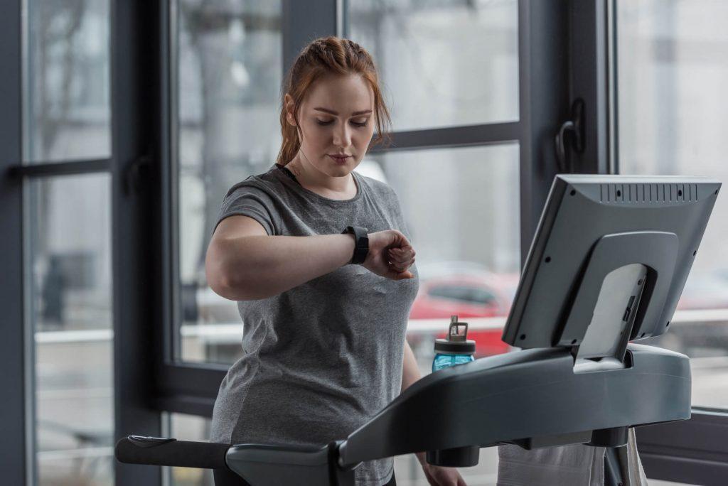 Mulher plus size olha o relógio no pulso após correr na esteira