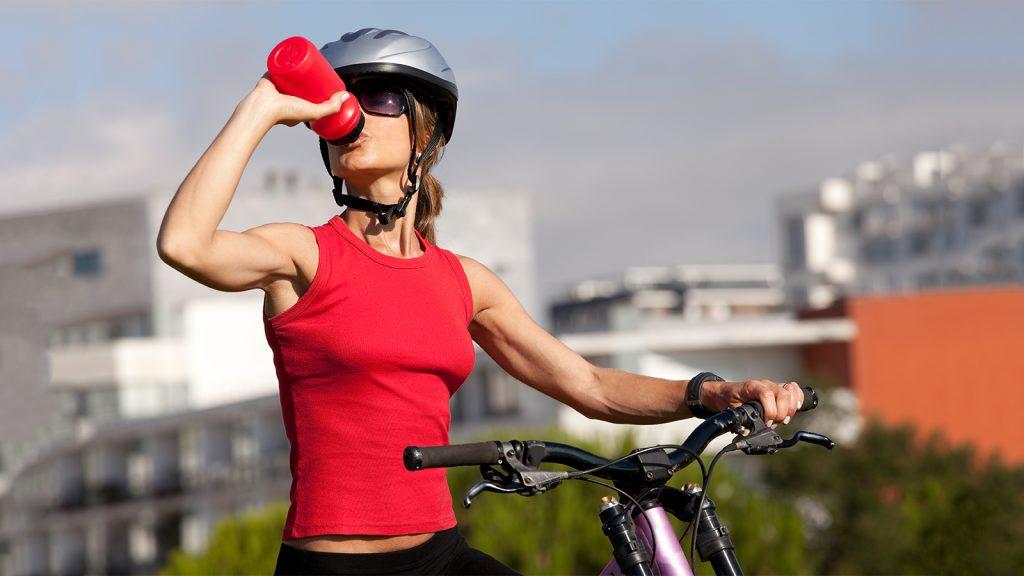 Mulher com capacete bebendo água enquanto anda de bike pela cidade