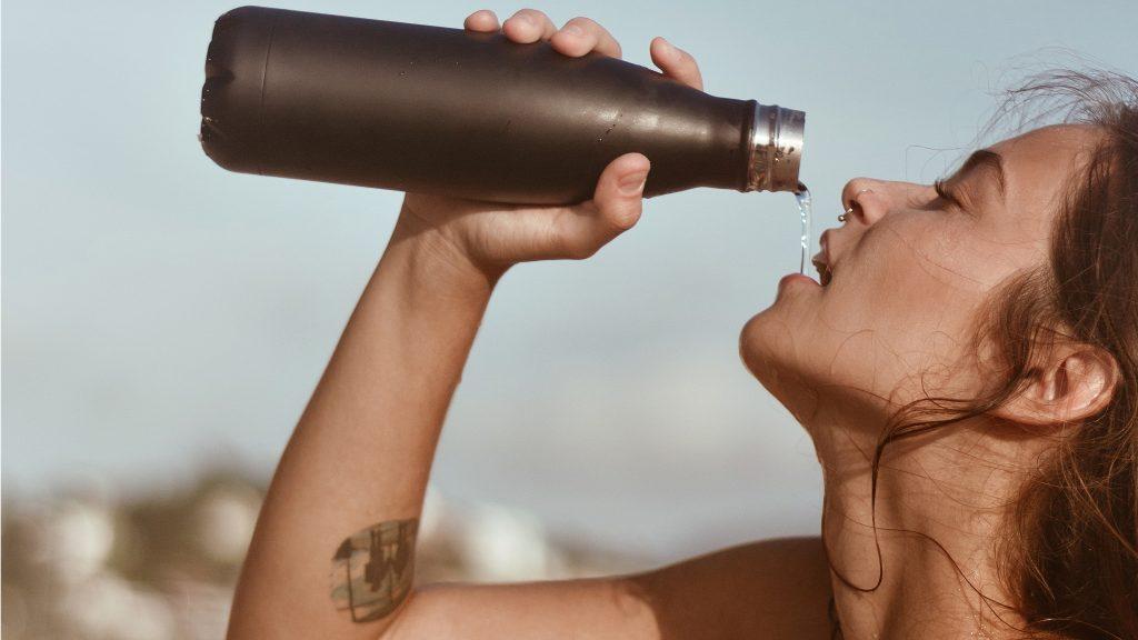 Mulher bebendo água numa garrafa