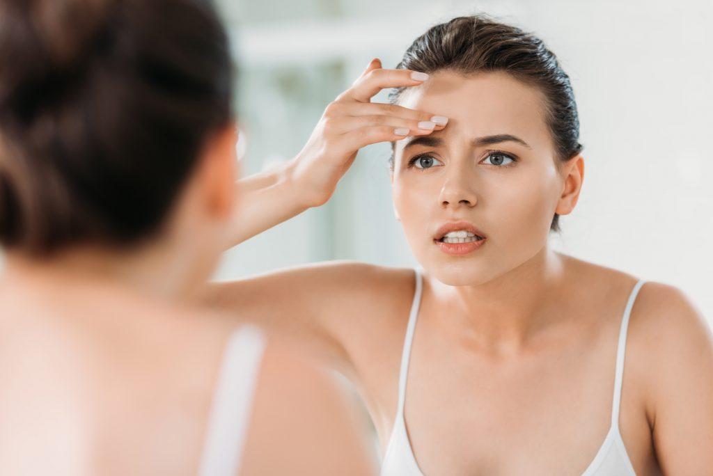 mulher-usando-creme-no-rosto-em-frente-ao-espelho