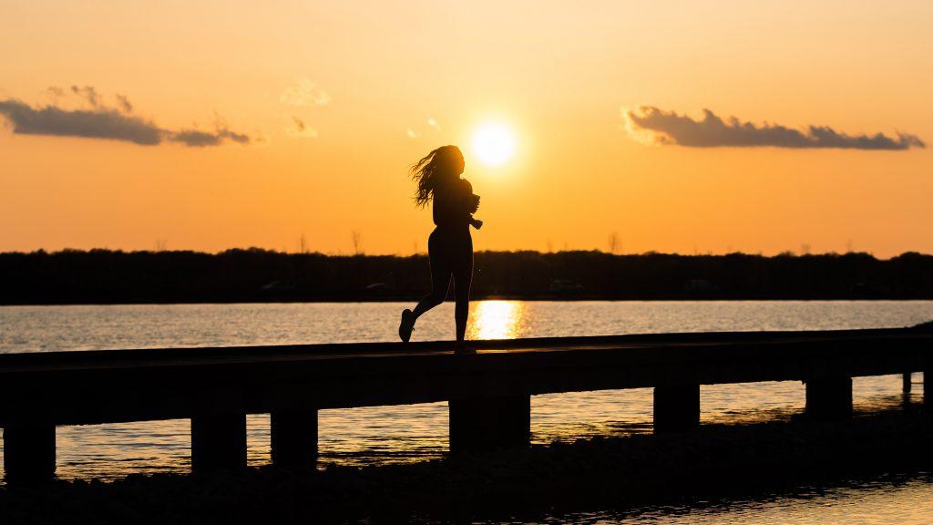 mulher-correndo-nascer-do-sol-como-acordar-cedo-para-treinar